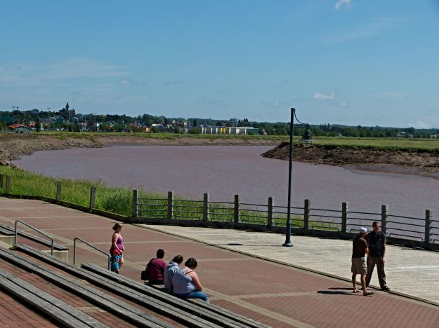 People waiting for the tidal bore to arrive. The river is a clay red in color.